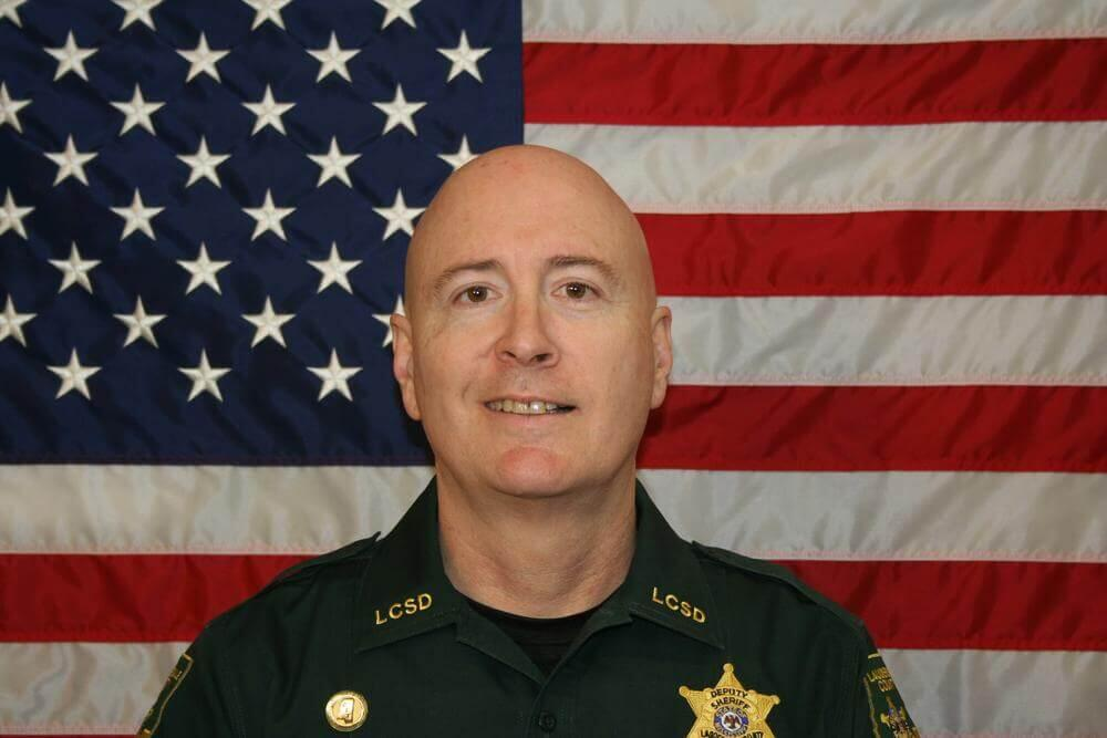 Chief Deputy Ward Calhoun standing in front of the flag of the United States of America.