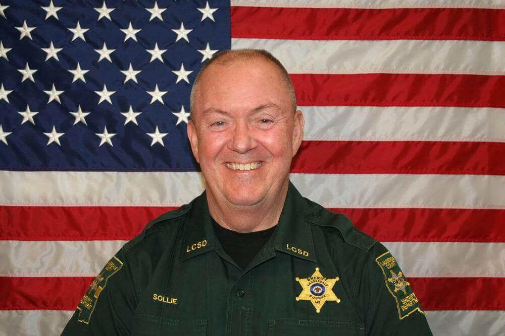Sheriff William D. Sollie standing in front of the flag of the United States of America.