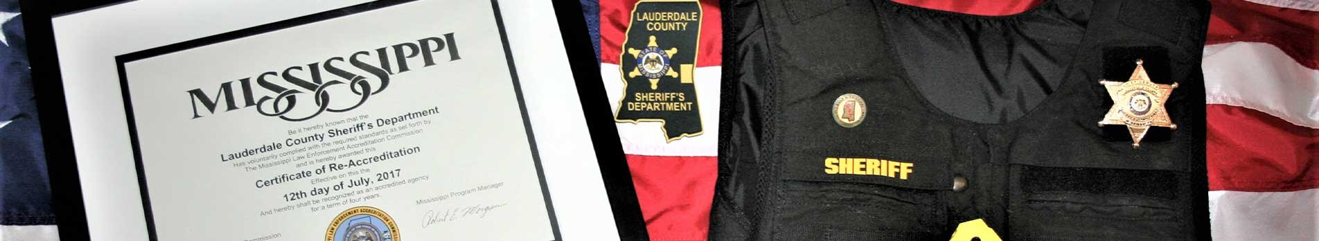 3 items resting against the Flag of the United States of America. Those items are a framed Certificate of Re-Accreditation, the Lauderdale County Sheriff's Department patch, and a bullet proof vest.